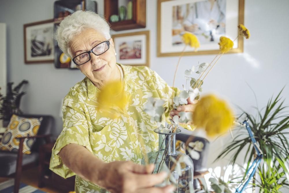 Elderly woman looking after flowers in vase