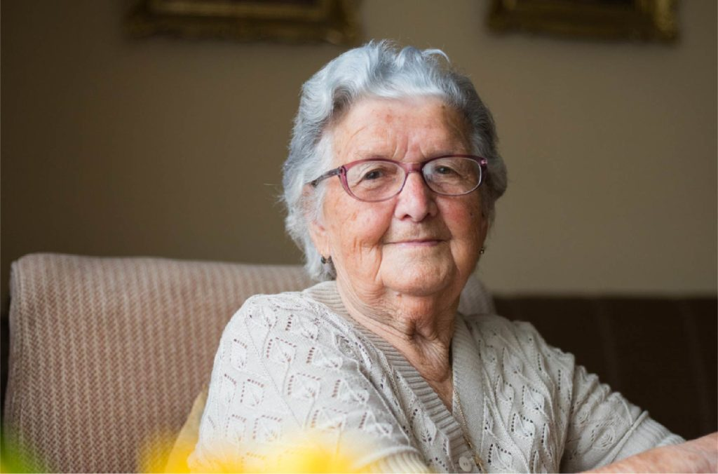 Elderly woman in chair looking into camera