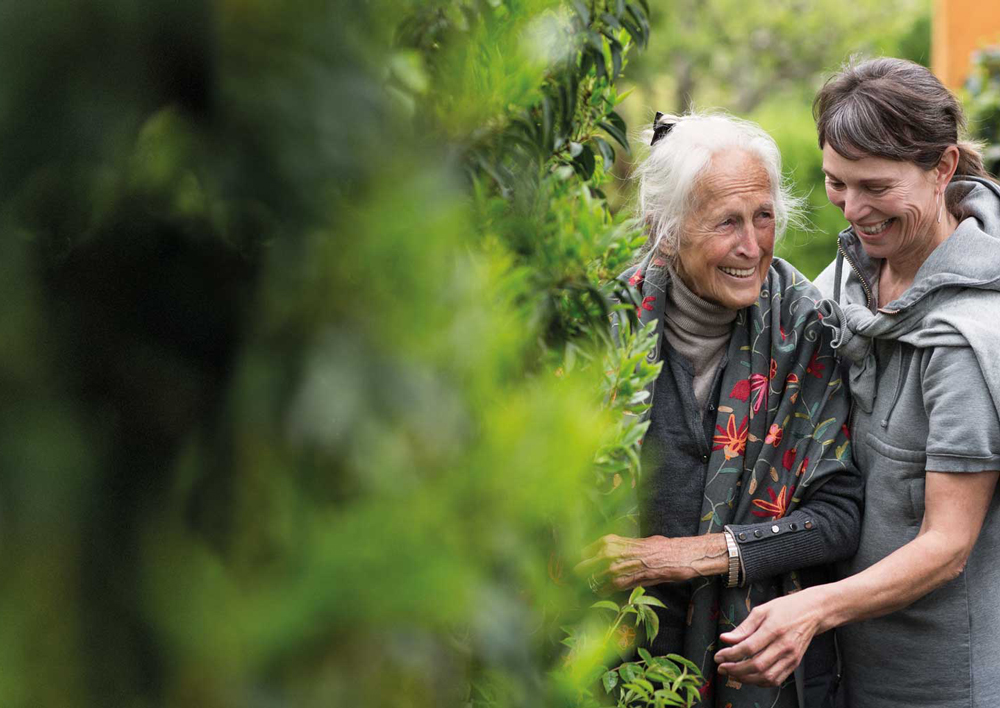 Elderly woman and daughter waling outdoors