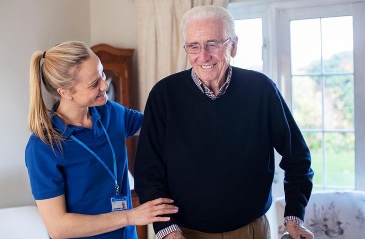 Senior Man Using Walking Frame With Care Worker
